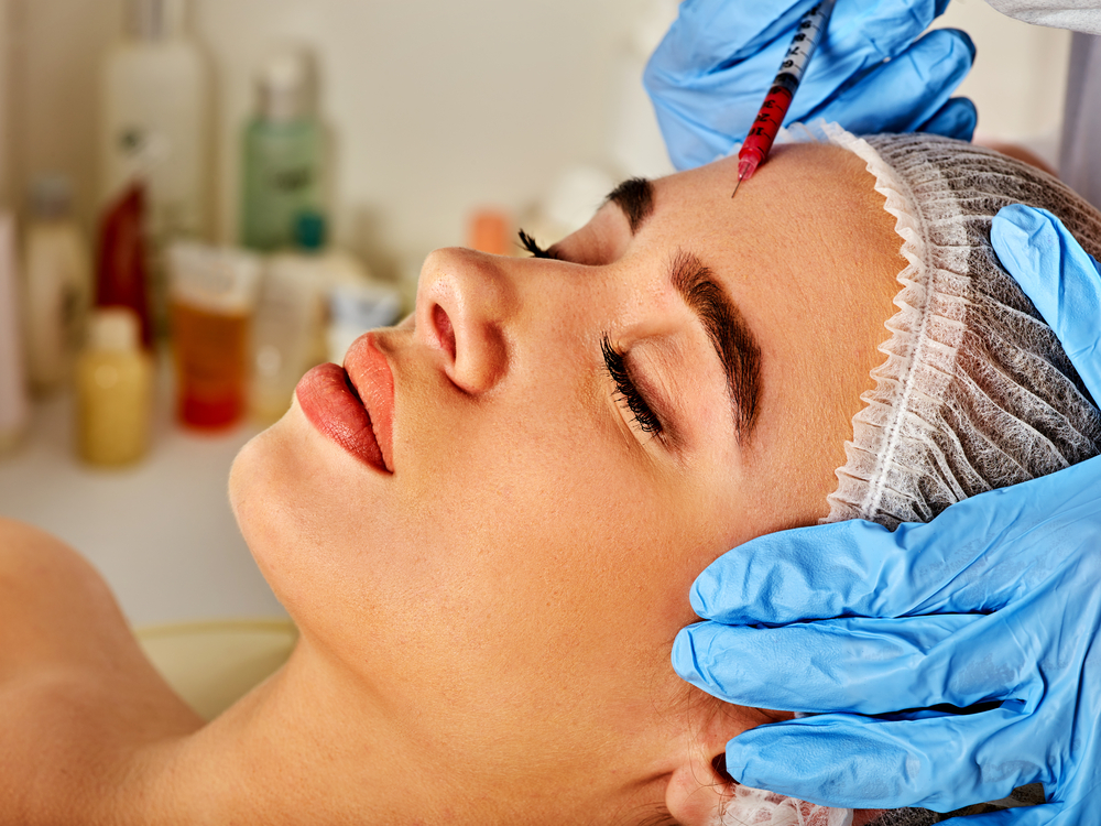Woman having botox injections in her forehead